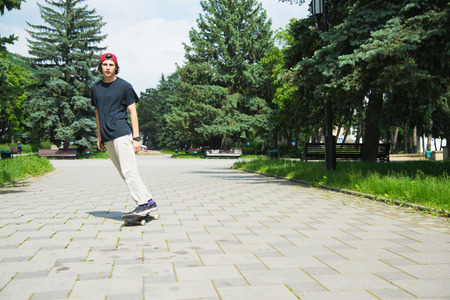 Long-haired skater-teenager in a T-shirt and a sneaker hat jumps an alley against a stormy sky Stock Photo