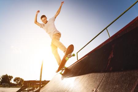 Tiener schaatser hangt over een helling op een skateboard in een skate park Stockfoto - 88202124