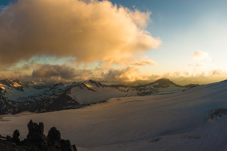 A sunset panorama of the elbrus and part of the Caucasian ridge with orange clouds and a cracked glacier at the bottom Stock Photo
