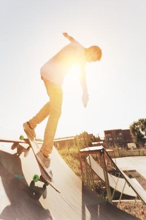 Patinador adolescente se cuelga sobre una rampa en un monopatín en un parque del patín Foto de archivo - 88328917