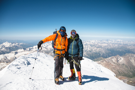 he: Portrait climber in a down jacket and harness he is standing next to his friend on the way to the top of a snow-capped mountain Stock Photo