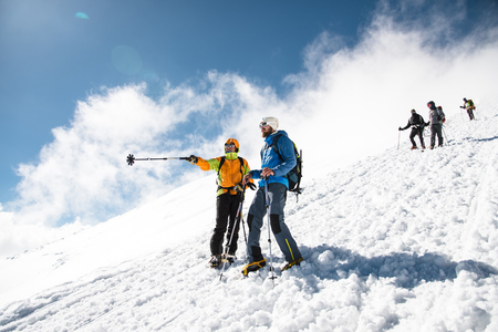 steep: fully equipped Professional climbers descend down the snowy slope in sunny weather