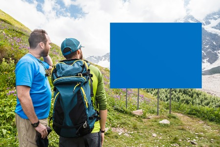 Mock up. Two tourists with backpacks stand in the mountains and look at the empty board.