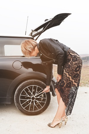 Beautiful blonde girl removing a wheel on the road outside the city Stock Photo
