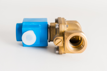 a new magnetic electro valve on a gray background. Hydraulic or pneumatic valve with electro-magnetic control