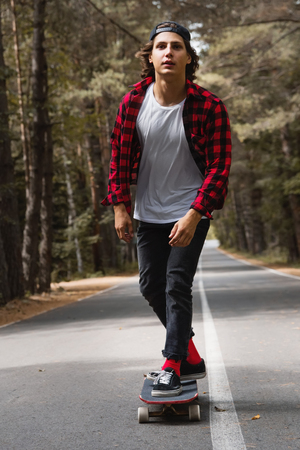 A young hipster in a cap and plaid shirt is riding his longboard on a country road in the forest