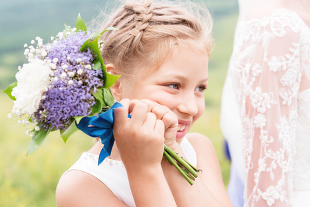 Un bambino piccolo e commovente e un meraviglioso bouquet da sposa di peonie bianche e viola alle nozze dei suoi genitori Archivio Fotografico - 90008009