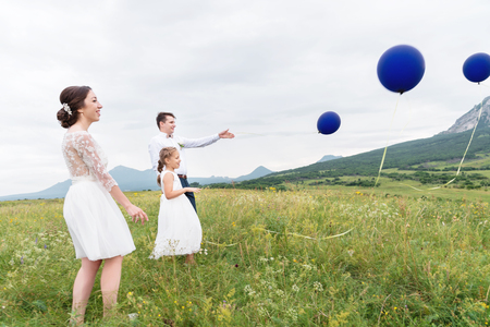 A young couple and their daughter in wedding dresses are walking in nature with balloons Stock Photo