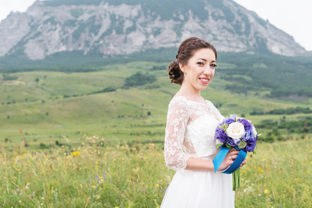 humilde: A beautiful Caucasian bride with a wedding bouquet of flowers in her hands Foto de archivo
