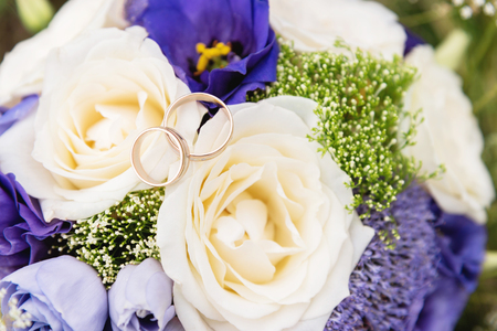 wedding gold rings lie on a wedding bouquet