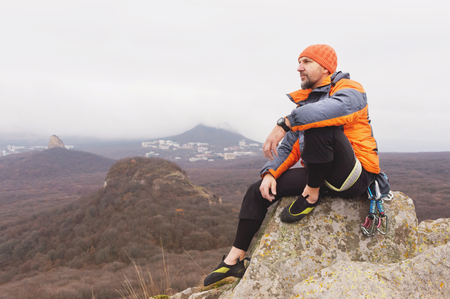 Hipster - a climber in a down jacket and a knitted cap sits and rests on the top of a rock Stock Photo