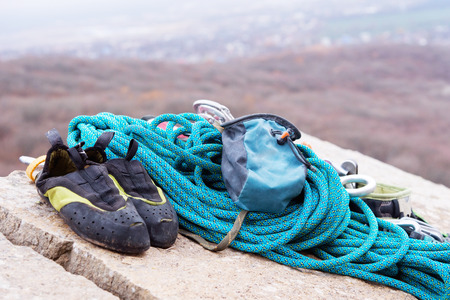 Climbing equipment - rope and carbines view from the side close-up. A coiled climbing rope lying on the ground as a background. Concept of outdoor sport