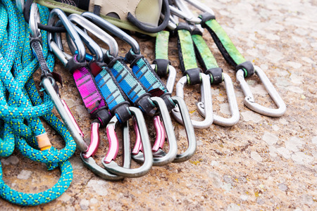 climbing equipment - a harness and a rope next to the carbines lie on a rock Stock Photo
