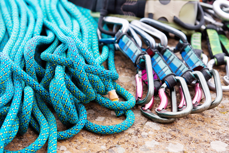 climbing equipment - a harness and a rope next to the carbines lie on a rock Stok Fotoğraf