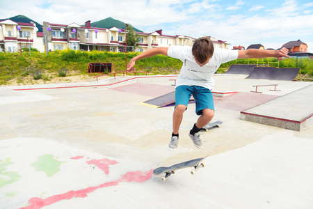A boy in a skate park doing a trick on a skateboard Stock Photo