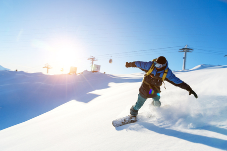 A snowboarder in a ski mask and a backpack is riding on a snow-covered slope leaving behind a snow powder against the blue sky and the setting sun