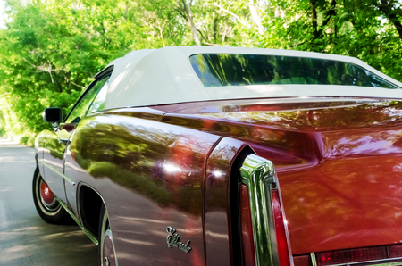 NEVINOMYSSC, RUSSIA - MAY 13, 2016: Automobiles. Offsite photography of old American cars. Cadillac Eldorado Convertible 1976s. Rear view of machine on a country road in a forest Editorial