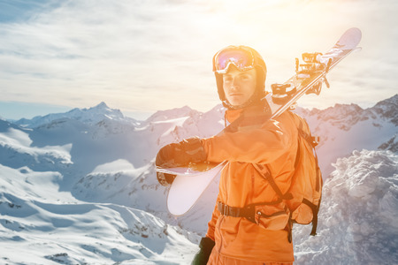 Portrait of a Skier in an orange overall with a backpack on his back and skis on his shoulders in a helmet stands on a rock against the blue sky. Stock Photo
