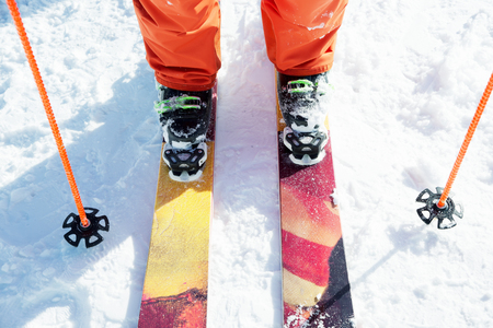 Legs athlete skier in an orange overall on a sport skiing on snow on a sunny day. The concept of winter sports