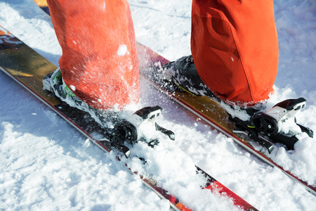 Orange alpine ski boots in a ski mount. One boot is completely fixed on skis, the second is not. Close-up. Orange suit