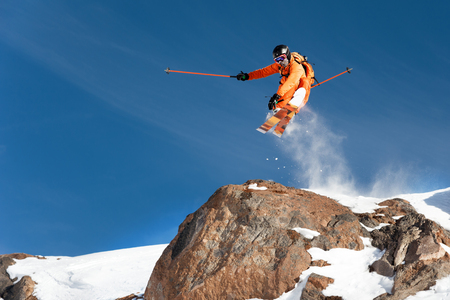 A professional skier makes a jump-drop from a high cliff against the blue sky leaving a trail of snow powder in the mountains. Photo from the slopes of Mount Elbrus. The concept of extreme sports and recreation in the mountains in winter. Copy the space. Jumping trick with grab