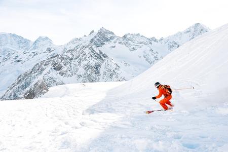 新鮮な雪の粉のスキー選手は、雪の斜面を下って急いでいます