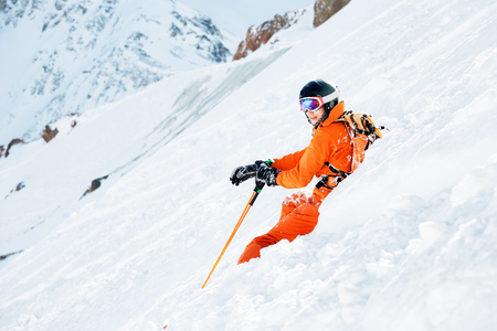 A skier in an orange overall and with a backpack is sitting happy in the snow after falling.