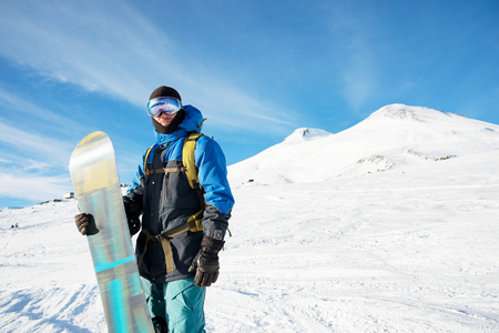 A professional snowboarder stands with his snowboard