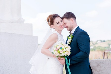 Portrait of a lovely couple honeymooned on a wedding day with a bouquet in hand against the background of an Orthodox Christian monument with angels.