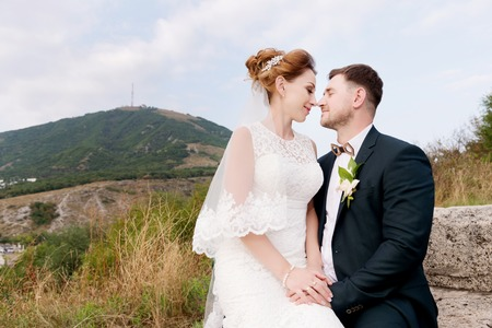 A loving couple of newlyweds sits on the background of the cityscape of a small resort town in the Caucasus. Newly married gently caress each other Banque d'images