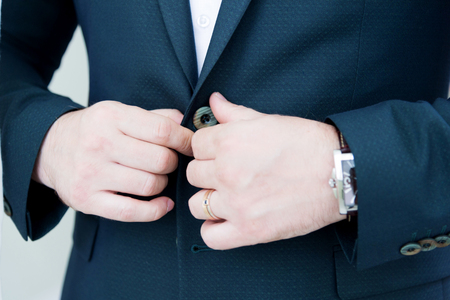 A stalwart newlywed with a beard in a suit fastens the button of his jacket. Super close-up.