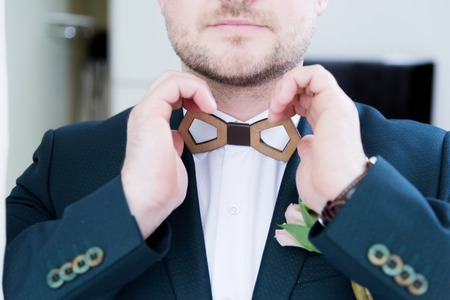 A sturdy newlywed with a beard in a suit adjusts the wooden bow tie on the collar with his white shirt.