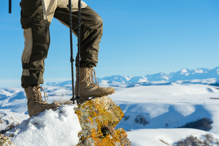 Close-up of a tourists foot in trekking boots with sticks for Nordic walking standing on a rock stone in the mountains