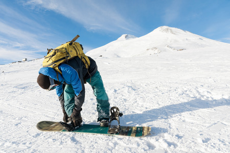 A snowboarder with a backpack on his back fastens snowboard bindings Stock Photo