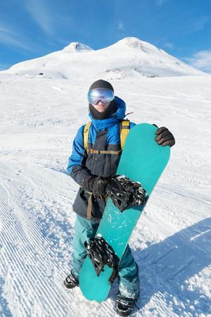 A professional snowboarder stands with his snowboard against the blue sky