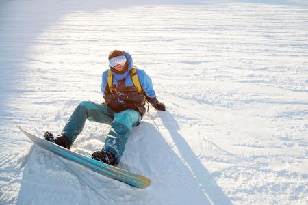 Smiling man snowboarder resting sit
