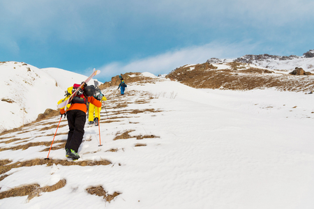A group of three freeriders climb the mountain for backcountry skiing along the wild slopes of the