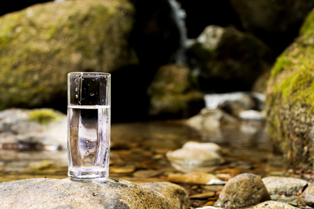 A transparent glass glass with mineral mountain river water stands on a stone beside the mountain river creek Stock Photo