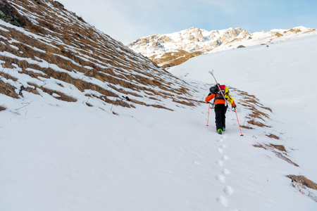 the ski freerider climbs the slope into deep snow powder with the equipment on the back fixed on the backpack.