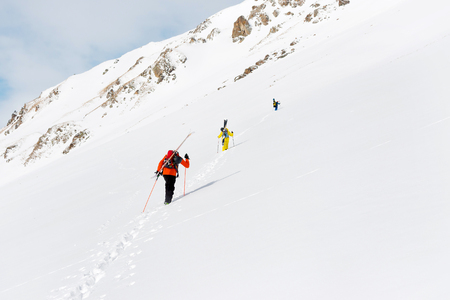 two ski freerider climbs the slope into deep snow powder with the equipment on the back fixed on the backpack.