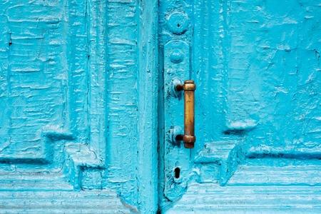 Close-up sleutelgaten met gordijnen en een handvat op de blauwe vaak geschilderd gebarsten houten deur met dubbele loop van de vorige eeuw met een spleet.
