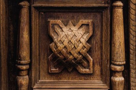 Vintage background. Elements of an old carved wooden door decorated with voluminous carved wooden elements imitating the weaving. A vintage concept of old antiques. Varnished old mahogany