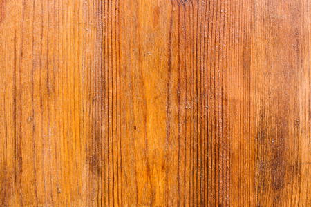 The background of the wooden varnished surface with the patterns of wood fibers appearing through the lacquer. Red wood. Aged wooden background structure
