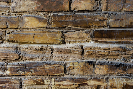 Textured background of old brick masonry pale yellow with deep horizontal scuffs.