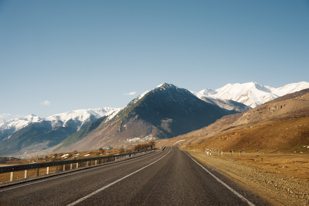 View of the autumn road leading to the mountains to the snow-capped peaks of the Caucasus.