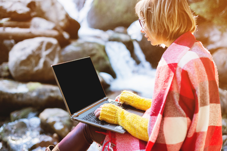 Mockup image of a girl wrapped in a plaid plaid with a laptop with a blank black desktop on her lap against the background of a mountain river and large stones. Stock Photo