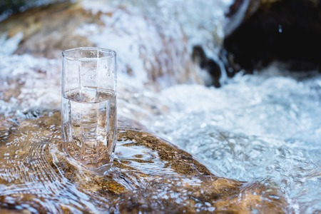 A glass glass with pure mountain drinking water stands on a rock in the course of a mountain river against the backdrop of seething cascades and waterfalls of a mountain river. The concept of pure mineral drinking water. Eco-friendly products healthy concept . Banco de Imagens