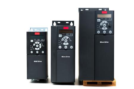 Un gruppo di tre diverse dimensioni e capacità nuovo inverter universale per il controllo della corrente elettrica e potenza per uso industriale su uno sfondo bianco isolato. Un convertitore di frequenza - raddrizzatore - stabilizzatore di potenza Archivio Fotografico