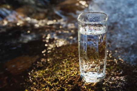 A transparent glass with drinking mountain water in sun light stands in the moss stone on sun beame against a background of a clean frost mountain river. The concept of drinking mountain drinking mineral water and the production of mineral environmentally friendly drinking water. Stock Photo