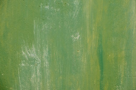 Textured metal surface carelessly colored green paint and faded in the sun in pale gray with rusty specks. Stock Photo